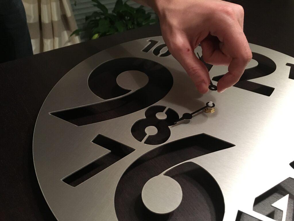 Mise en place des aiguilles du mécanisme au moment de créer une horloge design