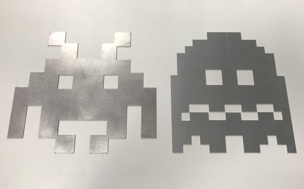 Pièces de métal découpées avec le nouveau configurateur de John Steel : formes spaces invader et fantome