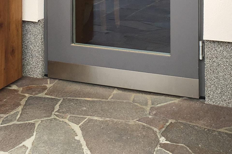 Protection d'un bas de porte en métal