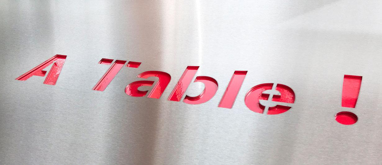 Dessus de table en inox avec découpe de lettres