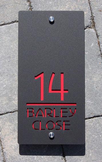 numéro de maison en métal sur fond rouge